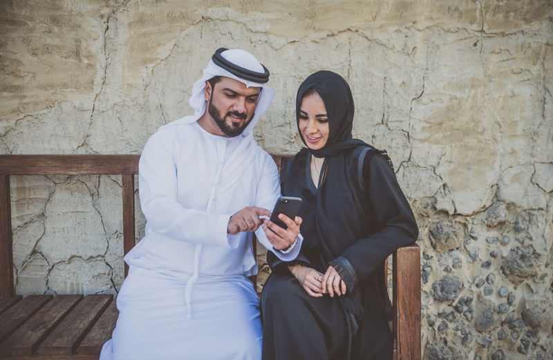 Couple wearing traditional clothing using smart phone while sitting on bench