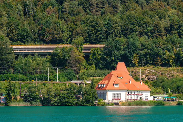 WORTHERSEE, AUSTRIA - AUGUST 08, 2018: Great scenery from the boat to the shore line of the lake, beautiful buildings, mountains, forests, highways. Tourists who enjoy a variety of water recreation types. Nature Day Outdoors Austria Carinthia Carinthian Lakes Tourist Tourists Lake Wörthersee Recreation  Leisure Landscape Water Sea Boats Motorboat Speedboats Summer People Holidays Fun Travel Beach Resort Lifestyle Sunny Rest Joy Waves Europe Alps Alpine Alpine Lake Architecture Tree Built Structure Plant Building Exterior Building No People House Green Color Residential District Land Waterfront Travel Destinations Forest