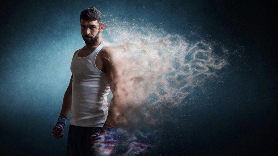Digital composite image of dissolving boxer standing against blue background