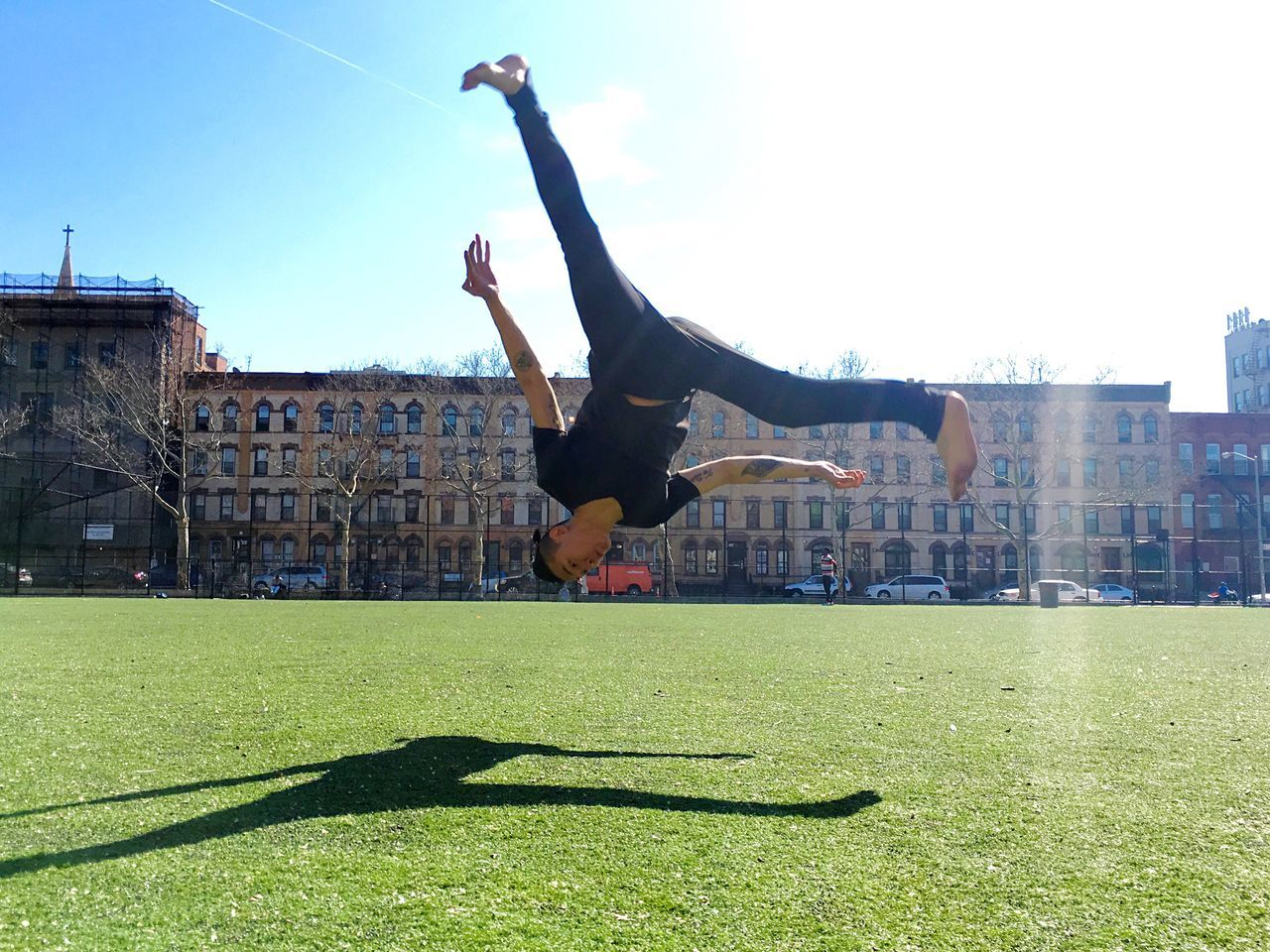 Man jumping in front of buildings against sky