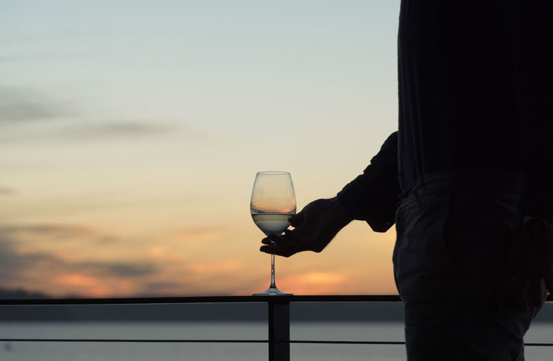 Silhouetted man with white wine glass outdoors at sunset.