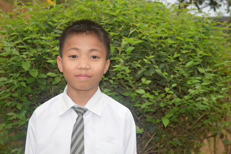 Portrait of boy in school uniform against plants