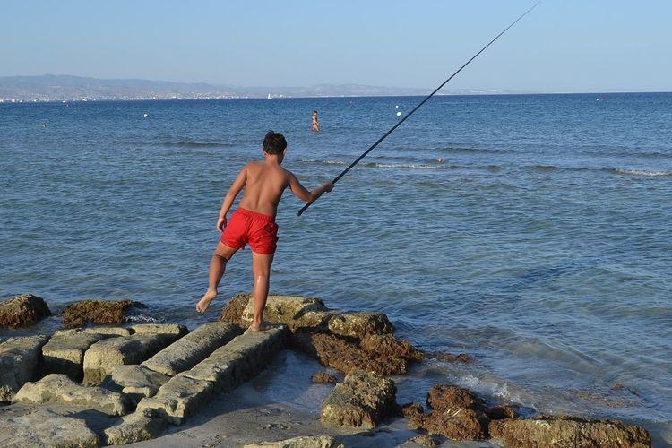 Rear view of shirtless man fishing in sea