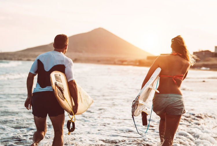 Happy friends carrying surfboards while walking on shore at beach