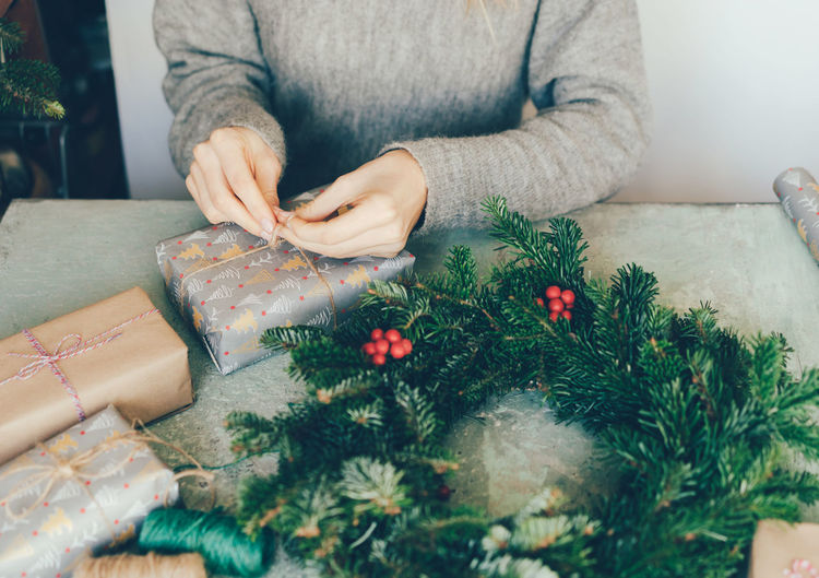 Woman makes a fir wreath and wrapping gifts for christmas. workshop crafting decorating.