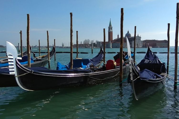 Gondolas moored on grand canal with san giorgio maggiore in background against blue sky