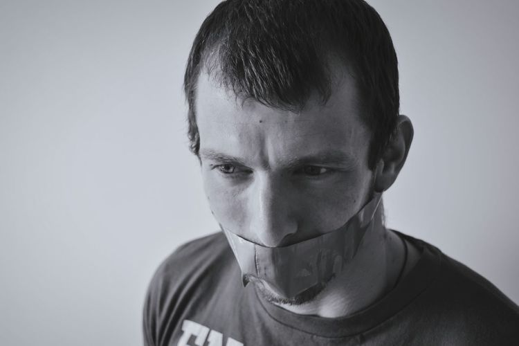Close-up of man with tape on mouth against gray background