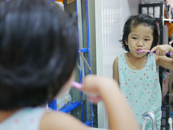 Girl brushing teeth while standing against mirror