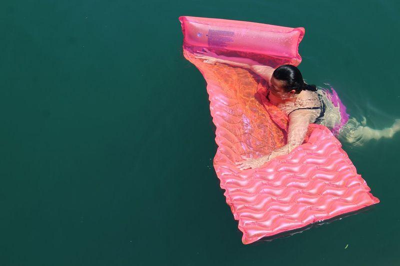Woman with pool raft swimming in sea