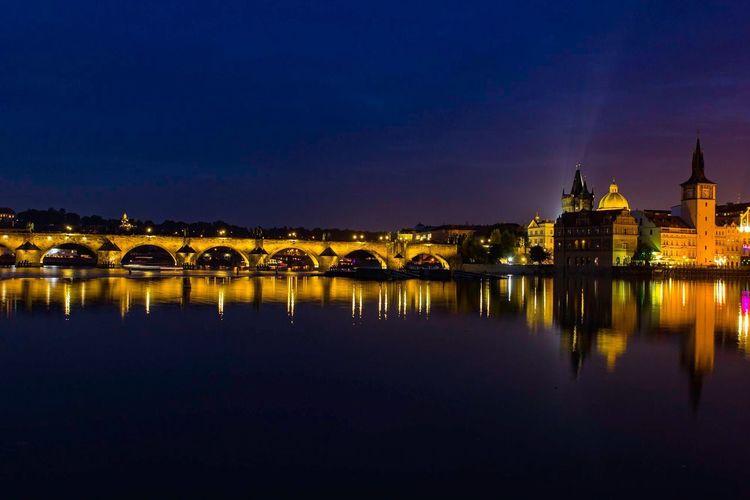 Illuminated charles bridge over river against sky at night