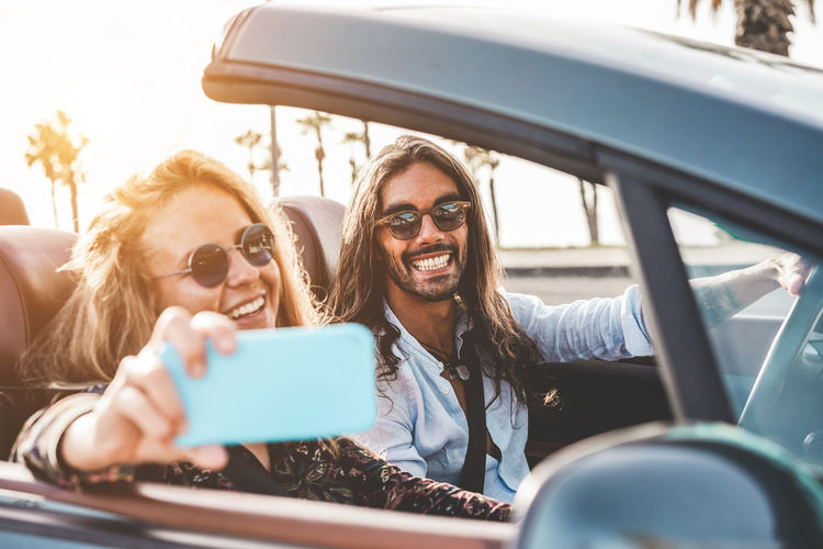 Happy woman taking selfie with boyfriend while sitting in convertible