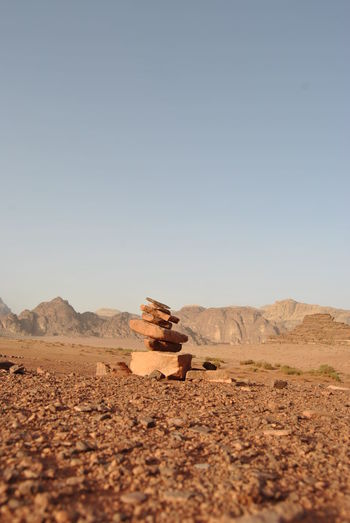 Stack Of Stones On Field Against Clear Sky