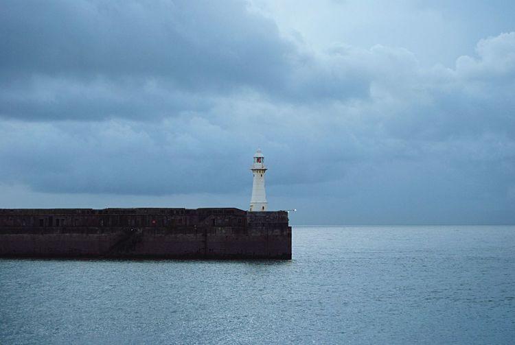 Lighthouse at sea against sky