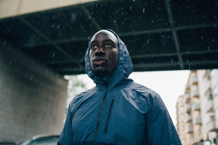 Portrait of man looking at camera during rainy season