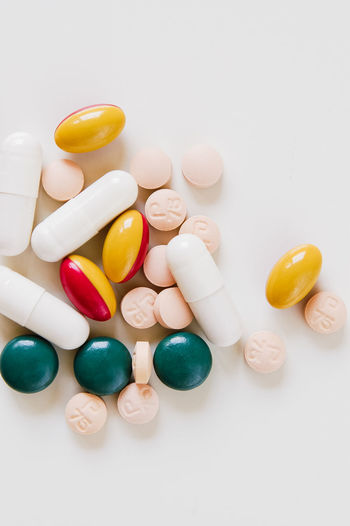 Various vitamin pills, medical capsules, supplements and drugs in tablet form in white, green, yellow, red and apricot on white background Medicine Pills Vitamins Addiction Close-up Medicine No People Nutritional Supplement Pill Studio Shot Studio Shot No People Tablets White Background