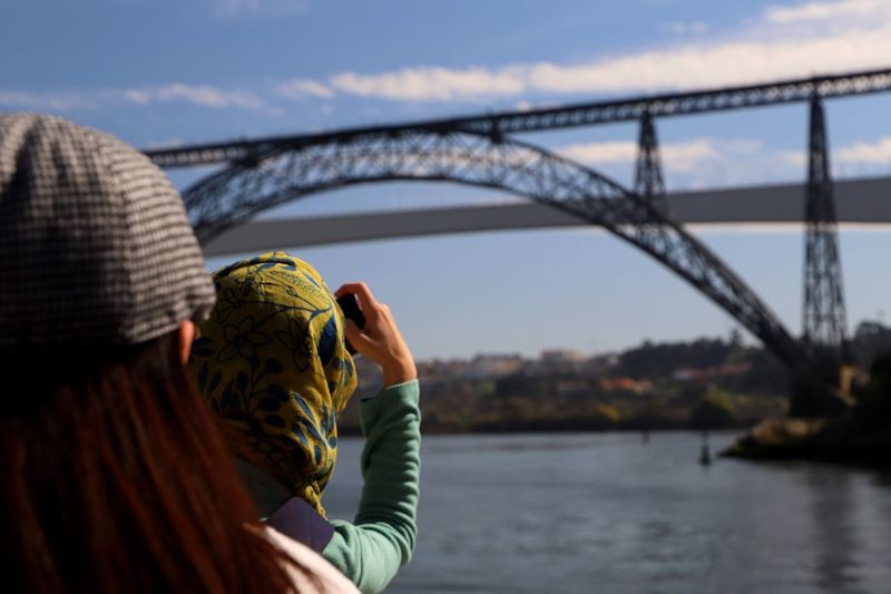 Friends photographing bridge and river against sky