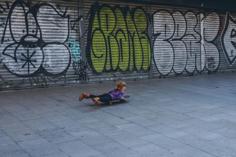 Full length of woman sitting on graffiti