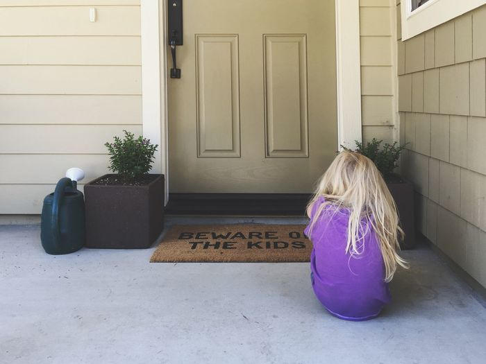Rear view of girl sitting outside house