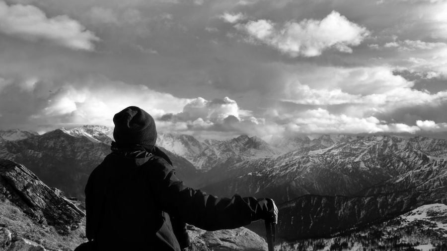 Rear view of man looking at snowcapped mountain against sky