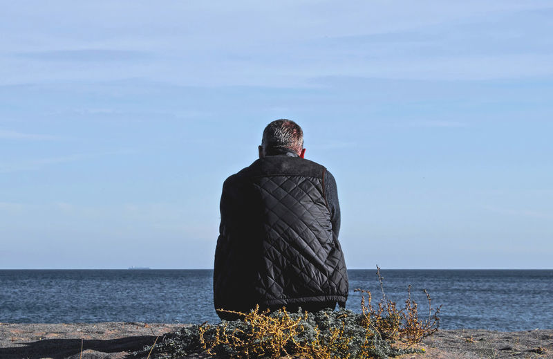 Single male sitting on beach looking out to sea with back to camera