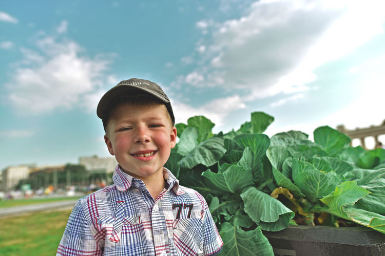 Portrait of smiling boy standing against sky