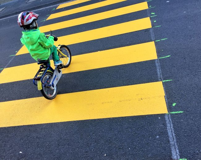 High Angle View Of Boy Riding Bicycle On Zebra Crossing