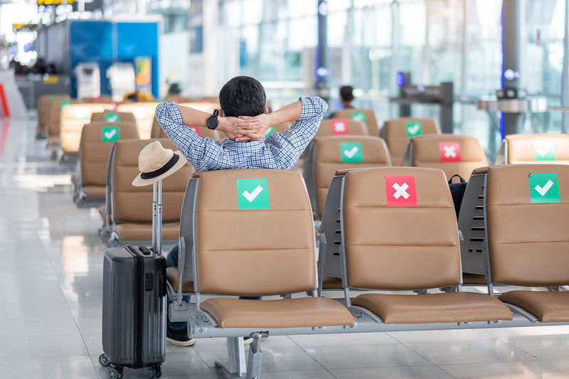 Rear view of man sitting on chair at airport