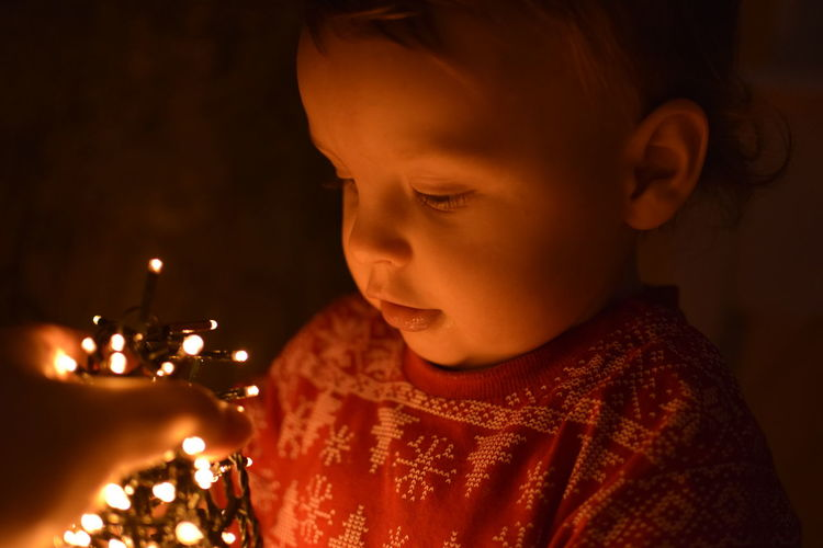 Close-up of boy with illuminated string lights