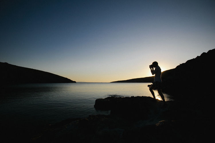 A tourist photographing during sunset at Syros Beach Beach Beauty In Nature Clear Sky Nature One Person People Photographing Real People Scenics Silhouette Silhoutte Photography Standing Sunset Syros Island Water