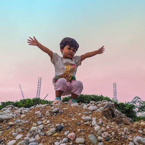 Low angle view of girl on rock against sky