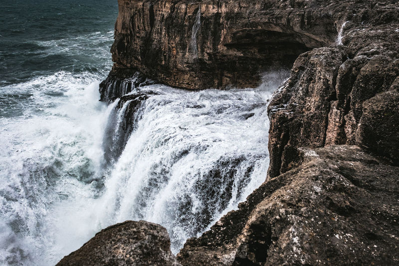 Rock Water Motion Rock - Object Solid Beauty In Nature Rock Formation No People Sea Scenics - Nature Nature Waterfall Flowing Water Day Land Aquatic Sport Power In Nature Power Outdoors Flowing Breaking Rough Sea Rough Waters Coastline Cliff