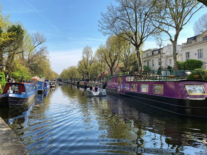 Boats moored in canal by city against sky
