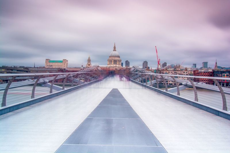 Digital composite image of bridge and buildings against cloudy sky