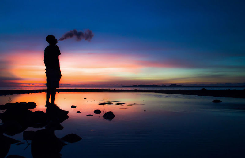 Silhouette man exhaling smoke at beach against sky during dusk