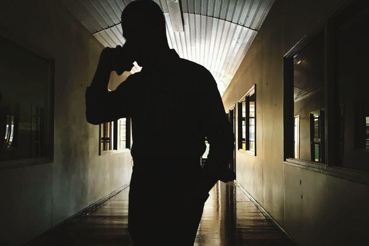 Silhouette man standing in corridor