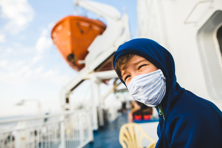 Boy wearing protective face mask while sitting in boat