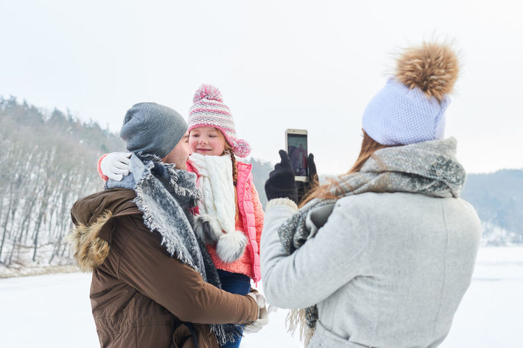 Woman Photographing Family In Warm Clothing Against Sky During Winter