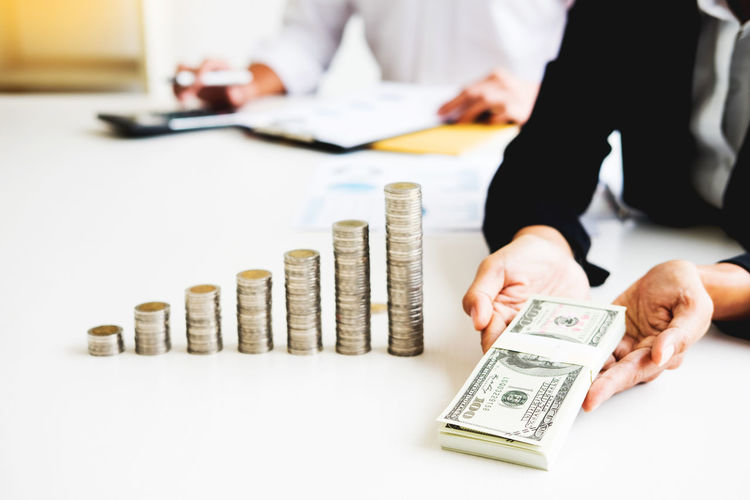 Midsection of business person with currency at desk in office