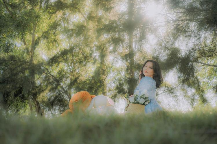 Full length of woman sitting on tree