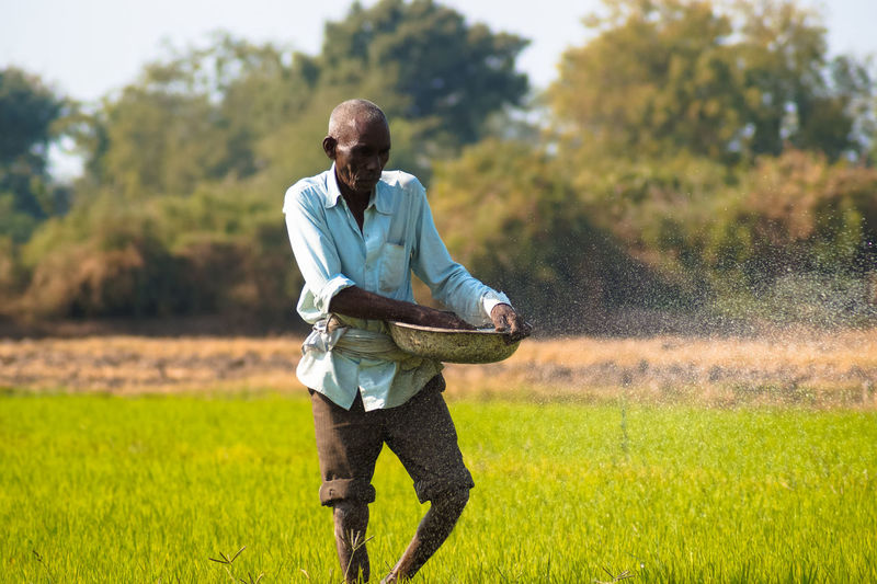 Farmer working while standing on field