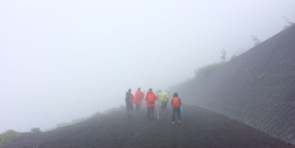 Rear View Of People Walking On Footpath During Foggy Weather