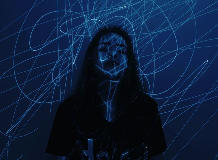 Blue Light On Young Woman Standing Against Wall