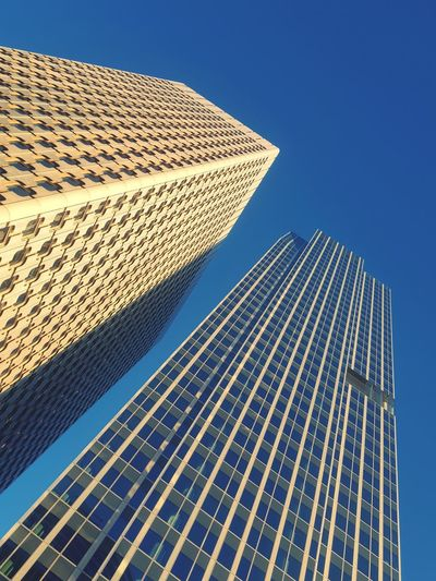 Low angle view of skyscraper against clear blue sky
