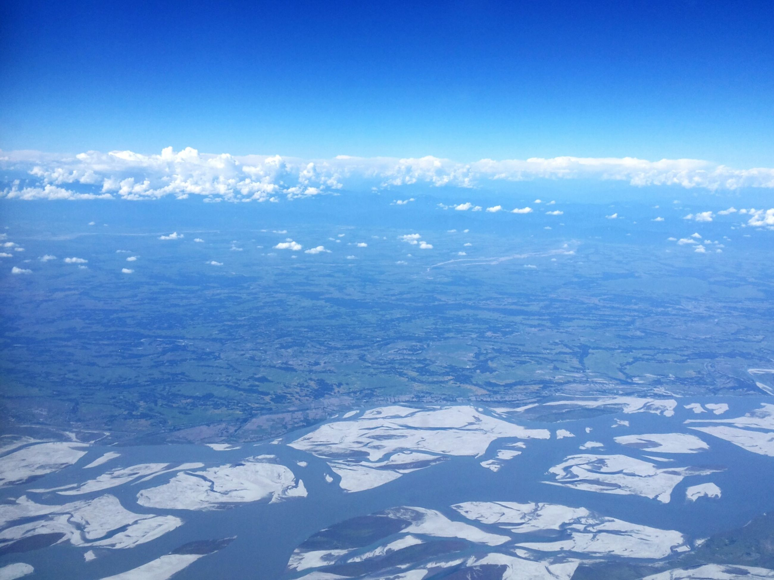 blue, aerial view, scenics, beauty in nature, tranquil scene, tranquility, nature, landscape, sky, copy space, idyllic, day, no people, white color, outdoors, flying, mountain, clear sky, cloud, majestic