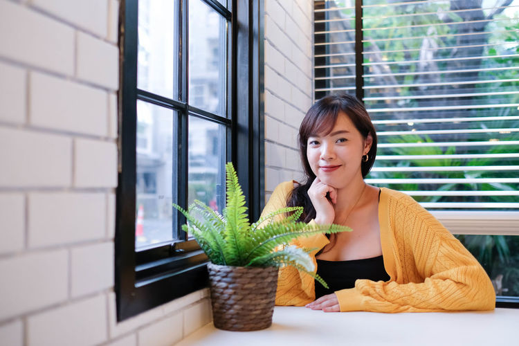 Portrait of woman with potted plants in window