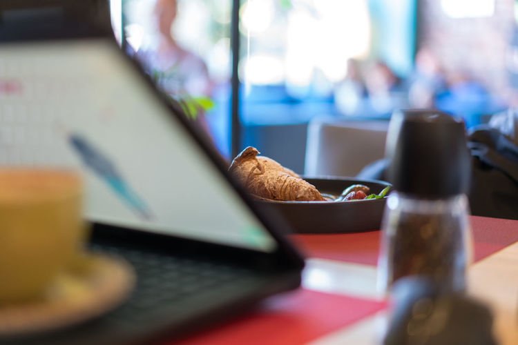 Bread Breakfast Business Close-up Communication Computer Connection Drink Focus On Foreground Food Food And Drink Freshness Indoors  Laptop No People Refreshment Selective Focus Still Life Table Technology Wireless Technology