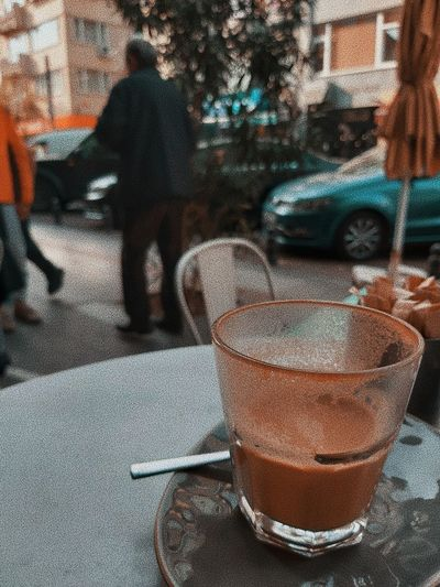 Glass of coffee on table in city