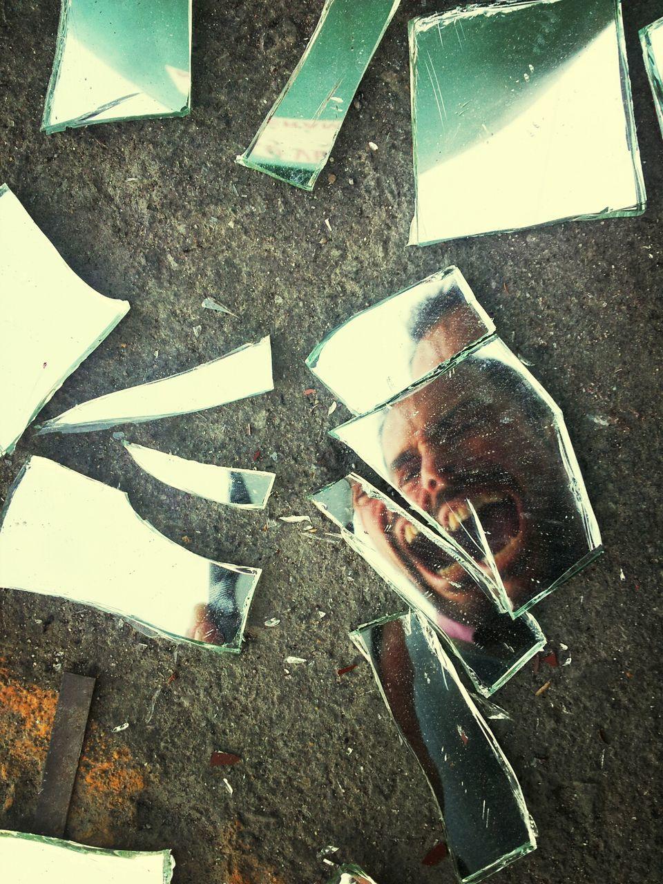 Reflection of man shouting on broken glass