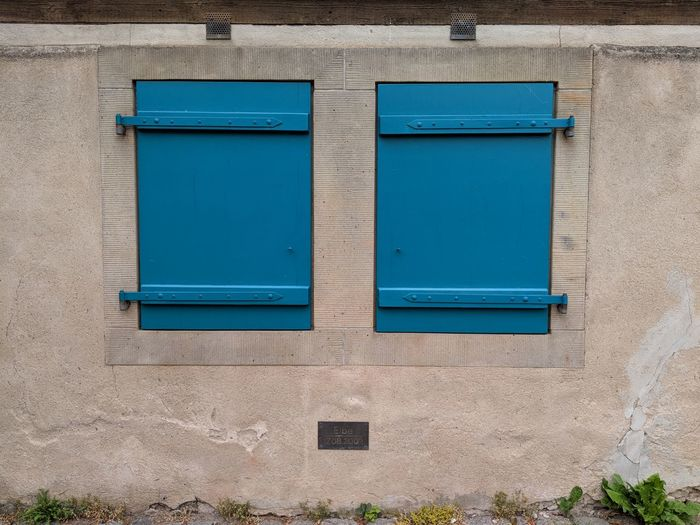 Blue window on wall of building