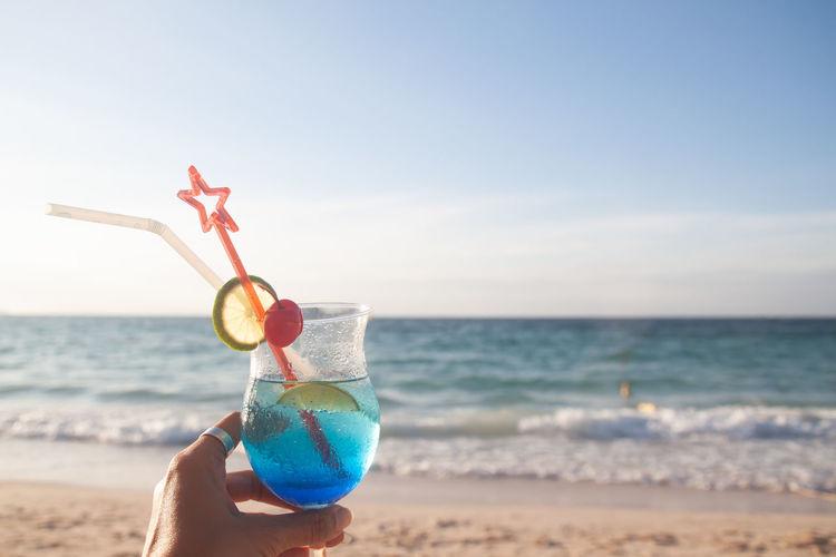 Person holding ice cream on beach